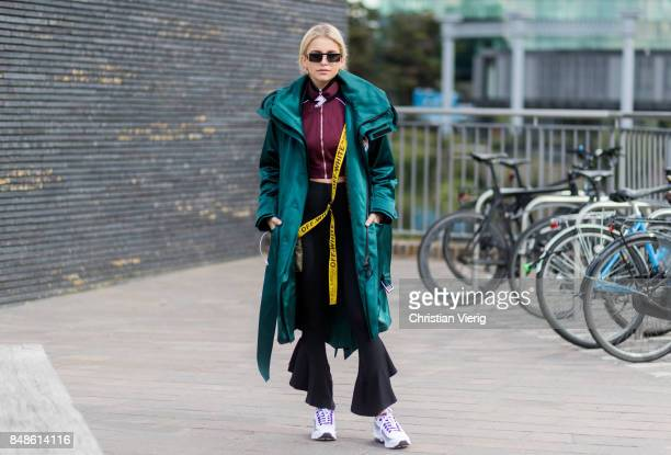 Caroline Daur wearing flared pants green coat cropped track suit jacket outside Versus Versace during London Fashion Week September 2017 on September...