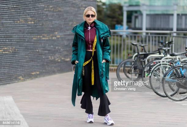 Caroline Daur wearing flared pants green coat cropped track suit jacket outside Versus Versace during London Fashion Week September 2017 on September...