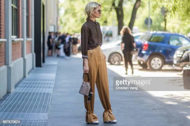 Caroline Daur wearing golden pants brown button shirt is seen outside Fendi during Milan Men's Fashion Week Spring/Summer 2018 on June 19 2017 in...