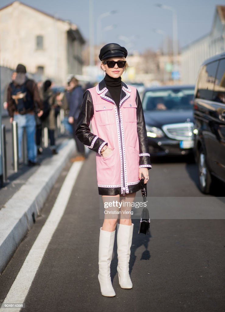 Caroline Daur wearing military leather hat, pink coat with leather sleeves, Prada bag, white boots, black turtleneck is seen outside DSquared2 during Milan Men's Fashion Week Fall/Winter 2018/19 on January 14, 2018 in Milan, Italy.