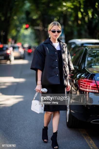 Caroline Daur wearing Prada ankle boots jacket dress white bag is seen outside Prada during Milan Men's Fashion Week Spring/Summer 2019 on June 17...