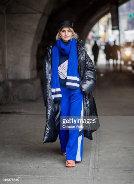 Caroline Daur wearing puffer coat bucket hat blue track suit pants blue scarf orange sneakers seen outside Tory Burch on February 9 2018 in New York...