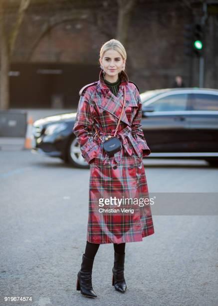 Caroline Daur wearing red plaid coat seen outside Burberry black mini bag during London Fashion Week February 2018 on February 17 2018 in London...