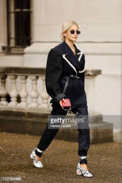 Caroline Daur wearing ripped edge suit, black leather belt and white heels outside Maison Margiela on September 25, 2019 in Paris, France.