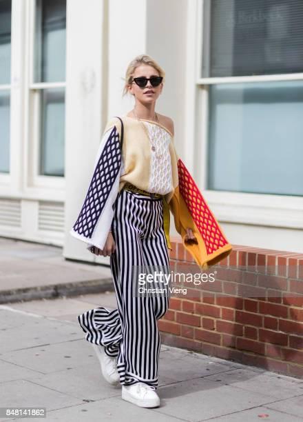 Caroline Daur wearing striped wide leg pants Off White belt knit Prada bag outside JW Anderson during London Fashion Week September 2017 on September...