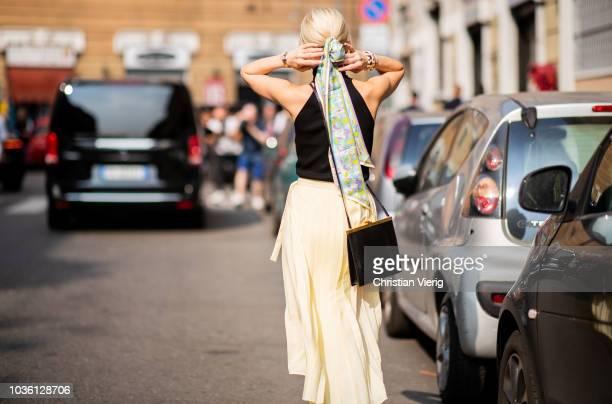 Caroline Daur wearing yellow skirt black top scarf in her hair is seen outside Jil Sander during Milan Fashion Week Spring/Summer 2019 on September...
