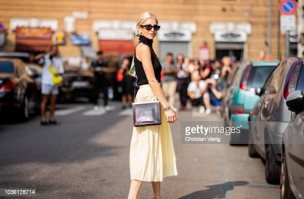 Caroline Daur wearing yellow skirt, black top, scarf in her hair is seen outside Jil Sander during Milan Fashion Week Spring/Summer 2019 on September...