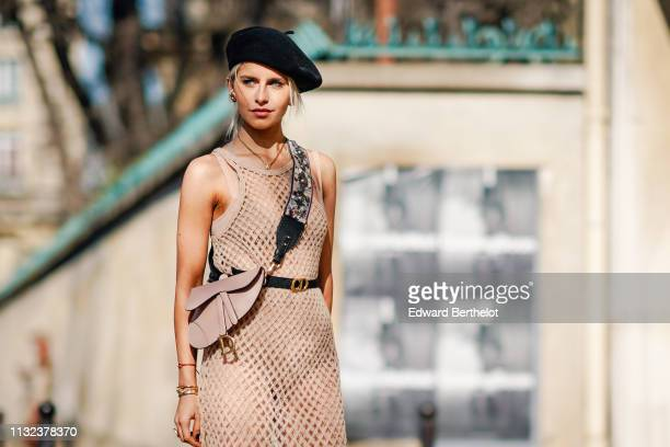 Caroline Daur wears a black beret hat a Dior Saddle pink bag a flower print shoulder strap a pink fishnet dress a CD Dior belt earrings outside Dior...