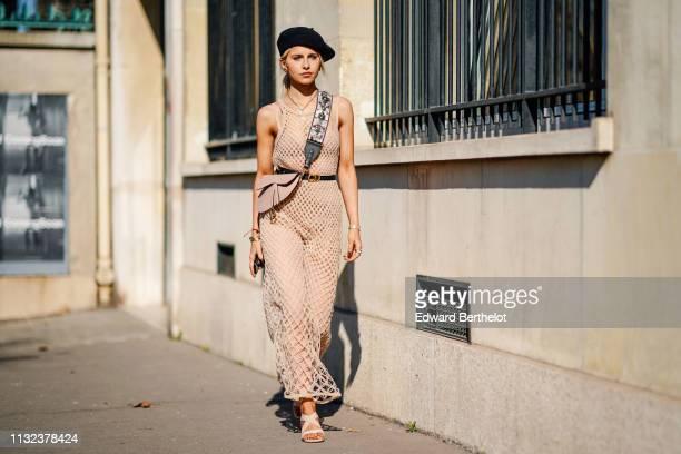 Caroline Daur wears a black beret hat, a Dior Saddle pink bag, a flower print shoulder strap, a pink fishnet dress, a CD Dior belt, earrings, outside...