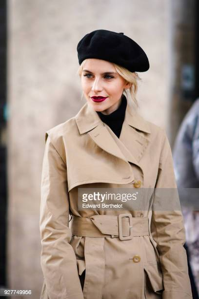 Caroline Daur wears a black beret hat a trench coat a red bag white boots outside Giambattista Valli during Paris Fashion Week Womenswear Fall/Winter...