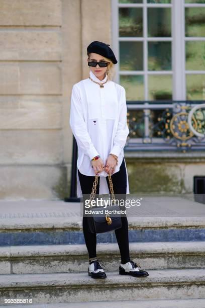 Caroline Daur wears a black beret hat a white shirt a Dior bag outside Dior during Paris Fashion Week Haute Couture Fall Winter 2018/2019 on July 2...
