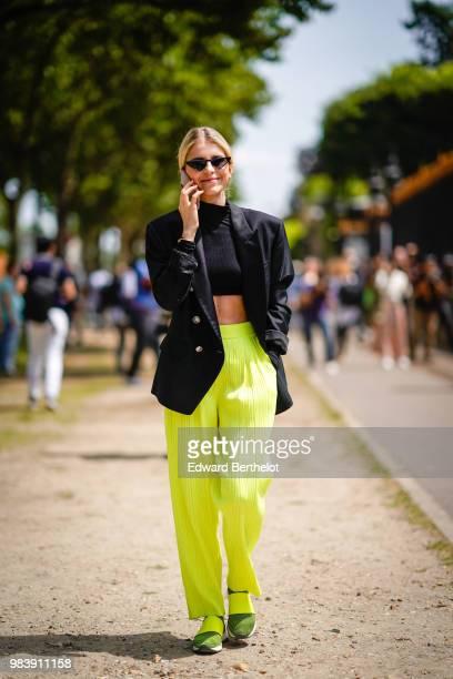 Caroline Daur wears a black blazer jacket a black cropped bare belly top yellow flared pants outside Balmain during Paris Fashion Week Menswear...