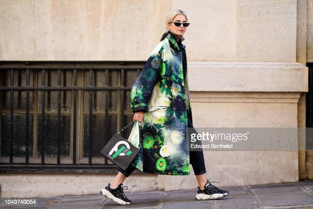 Caroline Daur wears a black coat with green prints a Prada bag outside Altuzarra during Paris Fashion Week Womenswear Spring/Summer 2019 on September...