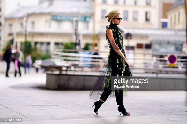 Caroline Daur wears a black lace mesh dress with green embroidery outside Giambattista Valli during Paris Fashion Week Womenswear Spring/Summer 2019...