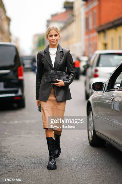 Caroline Daur wears a black leather jacket, a white top, a necklace, a skirt, black leather boots, outside the Boss show during Milan Fashion Week...