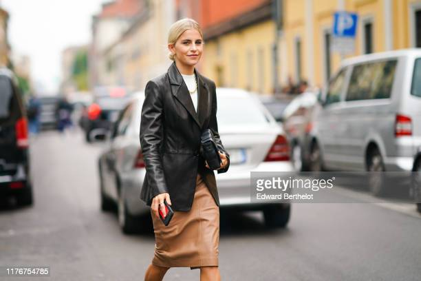 Caroline Daur wears a black leather jacket a white top a necklace a skirt black leather boots outside the Boss show during Milan Fashion Week...