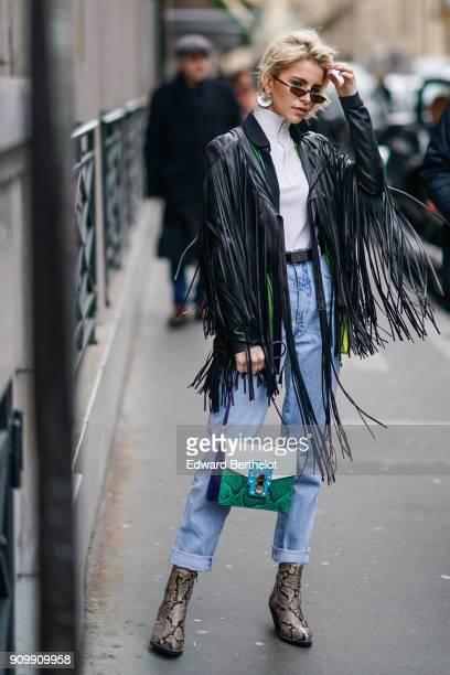 Caroline Daur wears a black leather jacket with fringes a green and white bag blue jeans snake print boots outside Elie Saab during Paris Fashion...