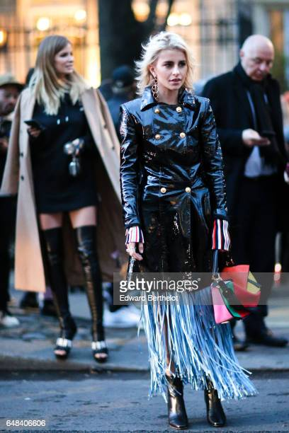 Caroline Daur wears a black vinyl coat a multicolor bag black leather boots and fringed skirt outside the Galliano show during Paris Fashion Week...