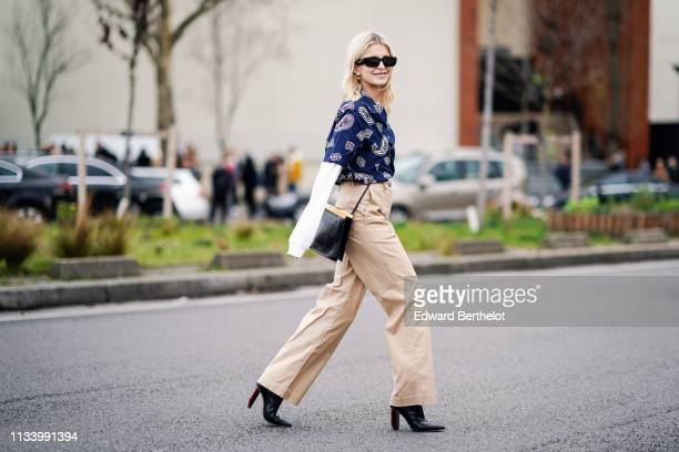 Caroline Daur wears a blue shirt with printed geometric patterns, beige flared pants, a white top, black shoes, sunglasses, outside Lacoste, during...
