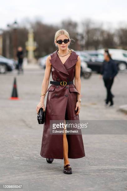Caroline Daur wears a burgundy leather double breasted dress, a belt, a clutch, leather shoes, a necklace, outside Dior, during Paris Fashion Week -...