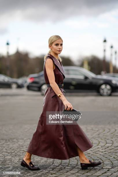 Caroline Daur wears a burgundy leather double breasted dress a belt a clutch leather shoes a necklace outside Dior during Paris Fashion Week...