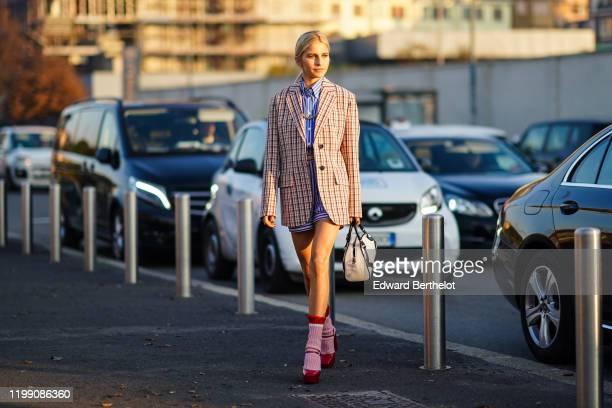 Caroline Daur wears a checked oversized blazer jacket, a Prada white and black bag, pink wool socks, red shoes, a blue striped shirt, outside Prada,...
