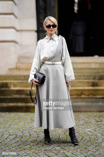 Caroline Daur wears a gray dress a belt a black bag sunglasses black shoes and attends the Nina Ricci show as part of the Paris Fashion Week...
