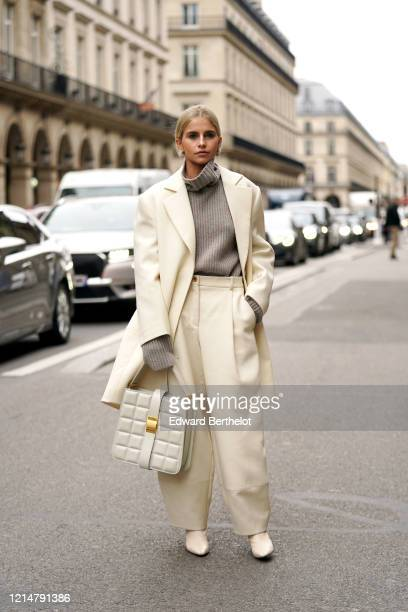 Caroline Daur wears a gray wool turtleneck pullover with long sleeves, a cream-color long oversized blazer jacket, a white quilted bag, pointy shoes,...