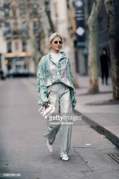 Caroline Daur wears a green and white shirt, flare pants, a white bag, sunglasses, outside Acne Studios, during Paris Fashion Week Menswear F/W...