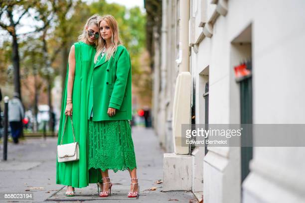 Caroline Daur wears a green dress sunglasses a white bag Charlotte Groeneveld wears a green jacket a green lace dress outside Valentino during Paris...