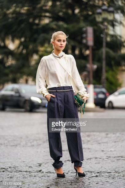 Caroline Daur wears a necklace, a white flowing shirt, navy blue striped pants, a green leather crocodile pattern Chloe bag, a belt, black high heels...