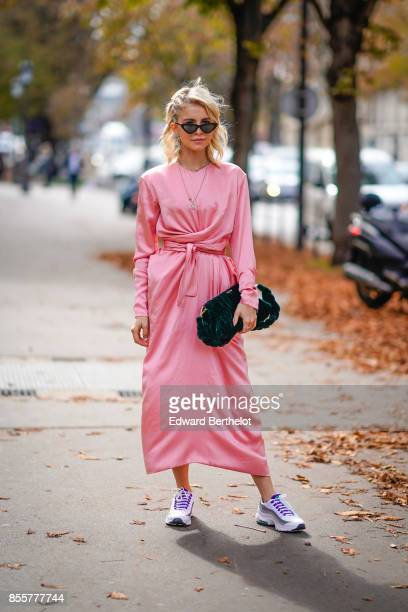 Caroline Daur wears a pink dress sneakers sunglasses a bag outside Issey Miyake during Paris Fashion Week Womenswear Spring/Summer 2018 on September...