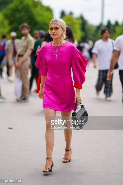 Caroline Daur wears a pink dress with ruffled sleeves, a black bag, a necklace, yellow sunglasses, a bracelet, outside Kenzo, during Paris Fashion...