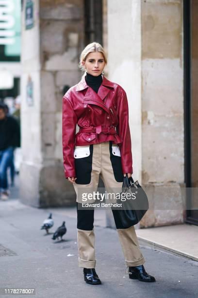 Caroline Daur wears a red leather jacket, black and white pants, a black bag, a black turtleneck, earrings, outside Giambattista Valli, during Paris...