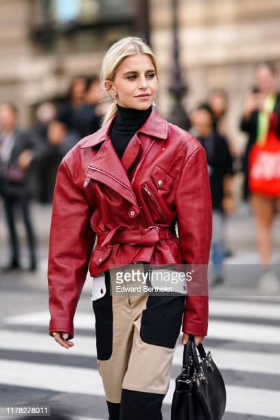 Caroline Daur wears a red leather jacket black and white pants a black bag a black turtleneck earrings outside Giambattista Valli during Paris...