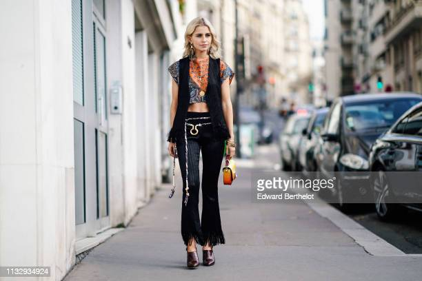 Caroline Daur wears a sleeveless jacket a bi color crop top with floral print flare ripped pants a Chloe bag shoes a necklace earrings outside Chloe...