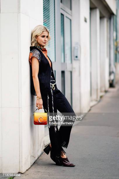Caroline Daur wears a sleeveless jacket, a bi color crop top with floral print, flare ripped pants, a Chloe bag, shoes, a necklace, earrings, outside...