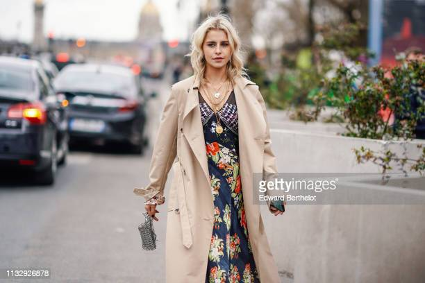 Caroline Daur wears a trench coat a floral print dress a silver bag a necklace outside Paco Rabanne during Paris Fashion Week Womenswear Fall/Winter...