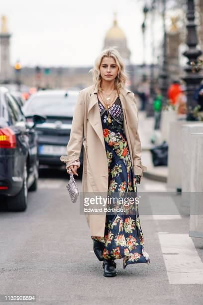 Caroline Daur wears a trench coat a floral print dress a silver bag a necklace outside Paco Rabanne during Paris Fashion Week Womenswear Fall/Winter...