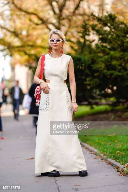Caroline Daur wears a white dress a red bag outside Moncler during Paris Fashion Week Womenswear Spring/Summer 2018 on October 3 2017 in Paris France