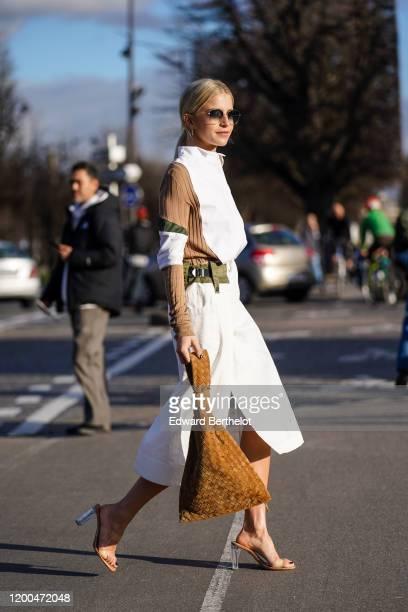 Caroline Daur wears a white khaki and brown dress, a brown triangular bag, high heeled shoes, outside Sacai, during Paris Fashion Week - Menswear F/W...