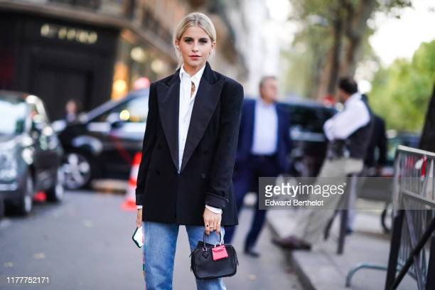 Caroline Daur wears a white shirt a black blazer jacket a bag with an attached pink mini bag blue cropped jeans outside Ralph Lauren during Paris...