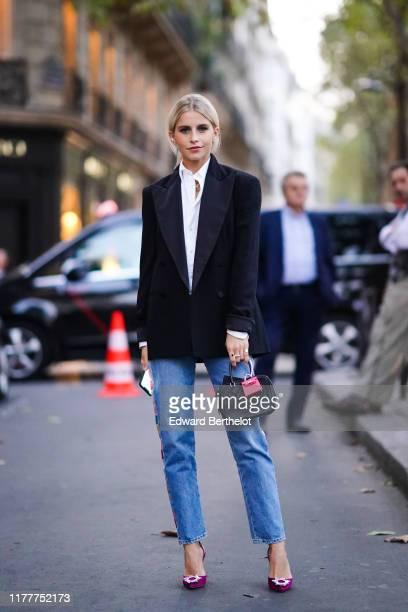 Caroline Daur wears a white shirt, a black blazer jacket, a bag with an attached pink mini bag, blue cropped jeans, purple shoes, outside Ralph...