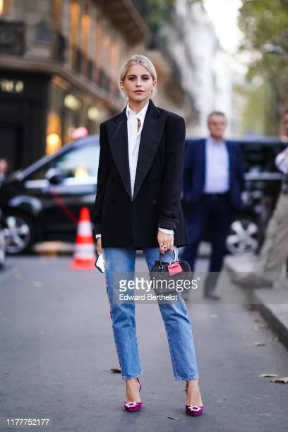 Caroline Daur wears a white shirt, a black blazer jacket, a bag with an attached pink mini bag, blue cropped jeans, purple shoes, outside Ralph...