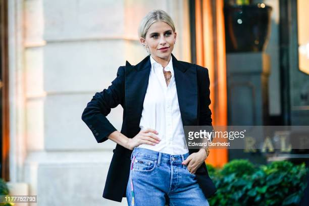 Caroline Daur wears a white shirt a black blazer jacket blue jeans earrings a necklace outside Ralph Lauren during Paris Fashion Week Womenswear...