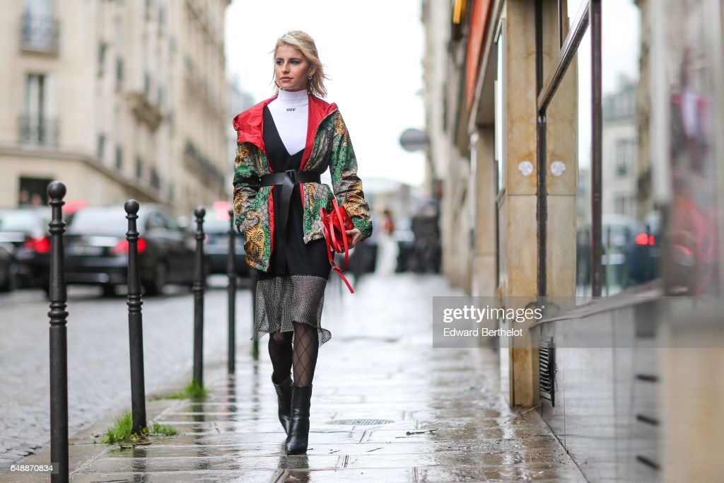 Caroline Daur wears a white turtleneck, a multicolor winter jacket with a hood and red inner lining, a black lace dress, black fishnet tights, and black leather boots, outside the Giambattista Valli show, during Paris Fashion Week Womenswear Fall/Winter 2017/2018, on March 6, 2017 in Paris, France.