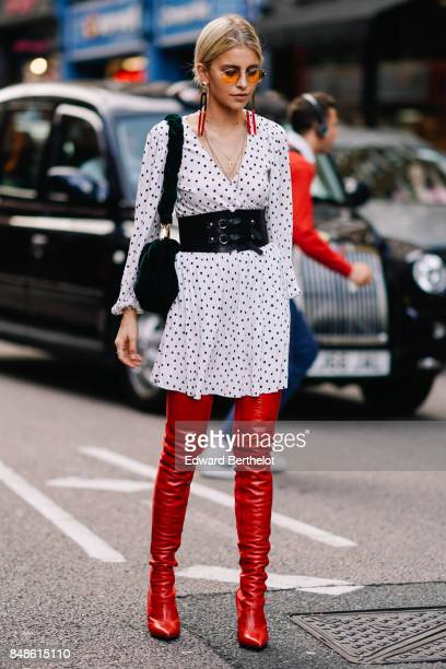 Caroline Daur wears a white v neck dress with black printed dots red leather thigh high boots a large black leather belt a bag outside Topshop during...