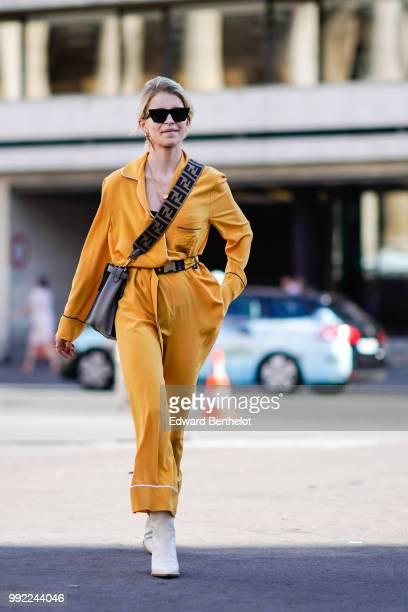 Caroline Daur wears an orange full outfit a shoulder strap bag white boots outside Fendi during Paris Fashion Week Haute Couture Fall Winter...