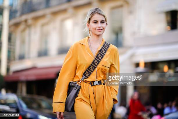 Caroline Daur wears an orange full outfit a shoulder strap bag white boots outside Fendi during Paris Fashion Week Haute Couture Fall Winter...
