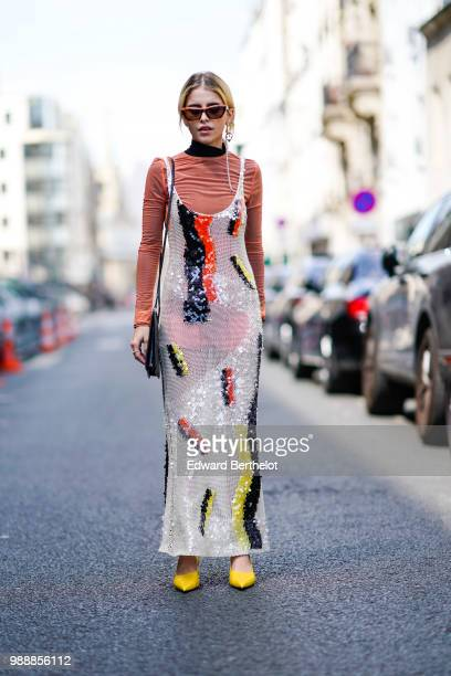 Caroline Daur wears an orange top a multicolor printed dress yellow shoes sunglasses a bag outside Acne Studios during Paris Fashion Week Womenswear...
